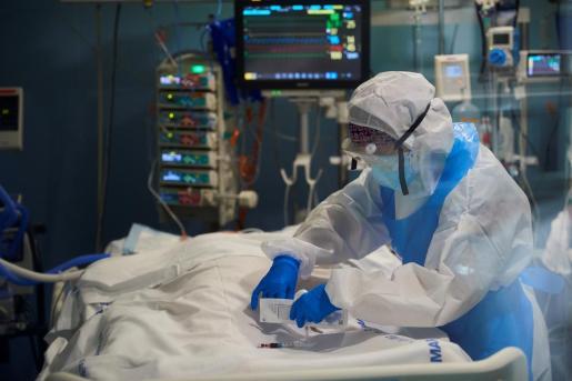 Un profesional sanitario toma una muestra de sangre a un enfermo de la COVID -19 en la UCI del hospital del Mar de Barcelona.