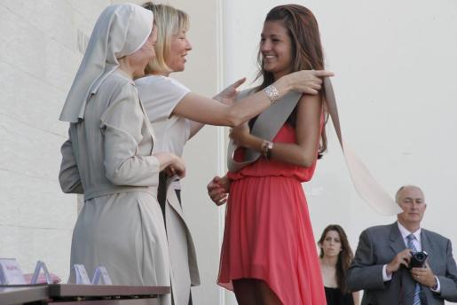 Una de las alumnas graduadas recibe su orla.