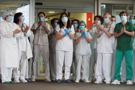 Un grupo de sanitarios aplaude a las puertas de un hospital.