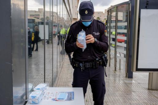 Un policía prepara mascarillas para repartirlas entre los usuarios de transporte público en la estación de autobuses de Ibiza.