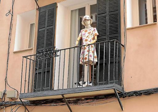 El maniquí de una mujer con un vestido floreado y lo que parece un perrito de cartón lleva tiempo en el balcón de una calle palmesana.