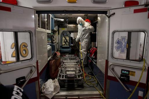 Personal médico desinfectando una ambulancia.