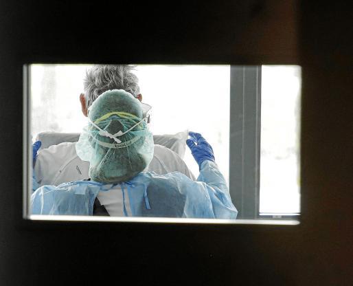Una enfermera atiende a un paciente con coronavirus ingresado en Son Espases.