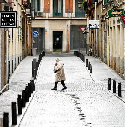 Una persona pasa por una calle vacía del centro de Madrid.