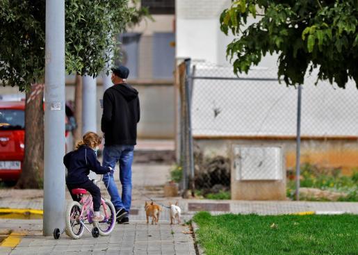 Un padre junto a su hija pasea a sus dos perros en una calle de Valencia.
