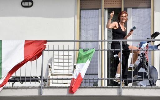 Una ciudadana de Bérgamo hace ejercidio en el balcón de su vivienda.