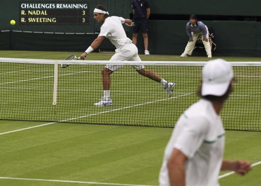 El tenista español Rafael Nadal devuelve una bola al tenista estadounidense Ryan Sweeting durante la segunda ronda del torneo de Wimbledon del pasado año.