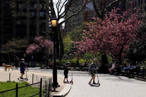 Tres niños, cubiertos con mascarillas, juegan con sus patinetes en el Madison Square Park de New York.
