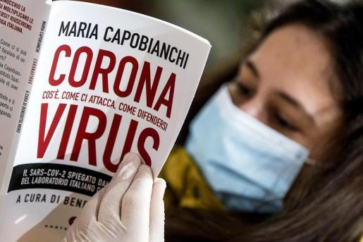 Una mujer leyendo un libro en una libreríaen Roma siguiendo las normas de seguridad.