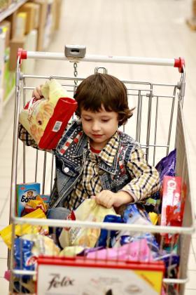 Un niño acompañando a sus padres a hacer la compra.