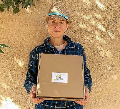 María Jover, una de las impulsoras de la iniciativa, y las cajas con los productos.