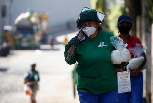 Una trabajadora, cubierta con mascarilla, acude a su puesto de trabajo en Manila.