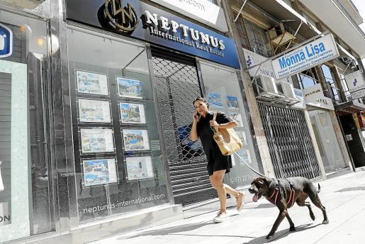 Una mujer paseando con su perro y hablando con el móvil. El Govern balear evita dar detalles sobre las medidas de desconfinamiento.