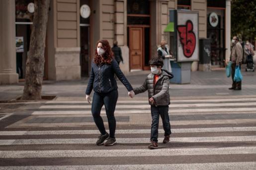 Una mujer acompañada de un niño cruza una calle en València.