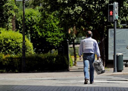 GRAFCVA4444. VALENCIA, 25/04/2020.- Un hombre camina por la céntrica calle Colón de Valencia portando un cartel en el que pide la dimisión del vicepresidente segundo Pablo Iglesias, este sábado cuadragésimo segundo día de confinamiento. EFE/Manuel Bruque Cuadragésimo segundo día de confinamiento
