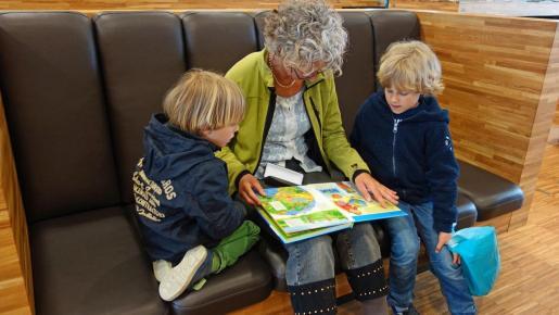 Una abuela, leyendo un libro a sus nietos.