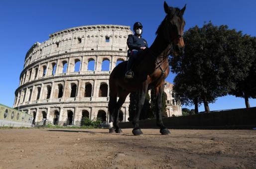 Un agente de la policía montada italiana frente al emblemático Coliseo de Roma.