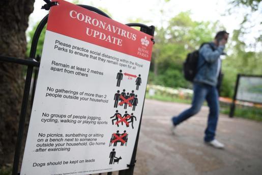 Un cartel con medidas contra el coronavirus en un paruqe de Londres