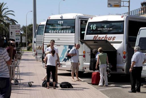 Un grupo de turistas sube a un autobús de transporte discrecional en el aeropuerto de Menorca.