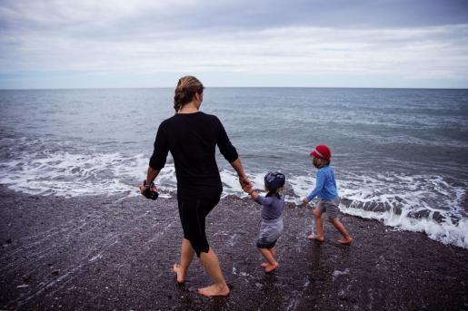 Una mujer con dos niños pasean por la playa de Torre de Benagalbón, en Rincón de la Victoria (Málaga.