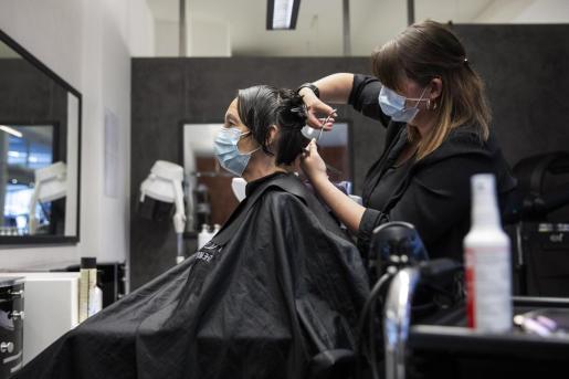 Una peluquera corta el pelo a una mujer con una máscara facial protectora contra el coronavirus. Hay muchas dudas sobre como afrontar la apertura.