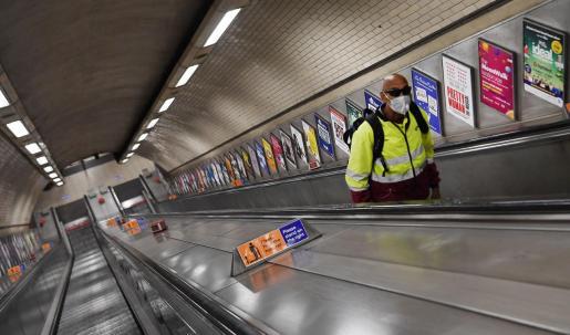 Un hombre con mascarilla solo en una estación de metro de Londres.