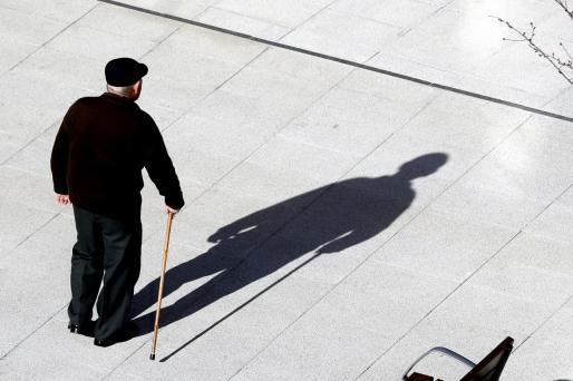 Un jubilado, camina por la calle.