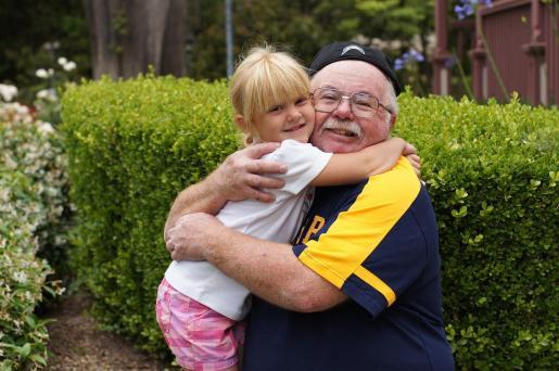Un abuelo y su nieta se abrazan.