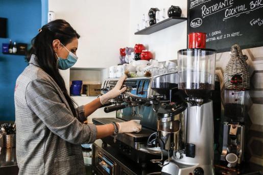 La propietaria de una cafetería de Roma sirviendo un café.