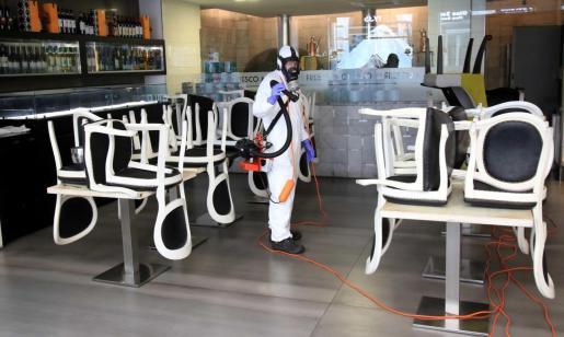 Un trabajador desinfectando un local en Milán.