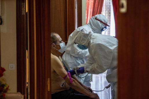 El equipo sanitario atendiendo a una persona mayor.