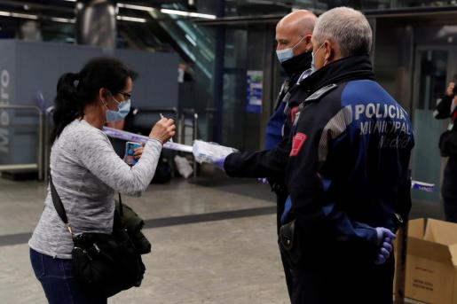 Policías entregan una mascarilla a una mujer en la estación de metro de Nuevos Ministerios en Madrid, el pasado 13 de abril.