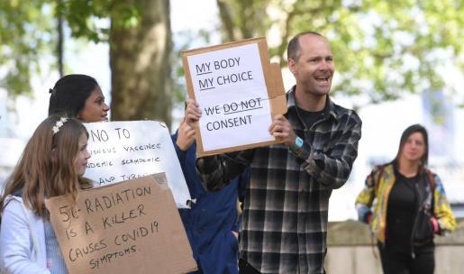 Manifestantes protestan con pancartas en la mano durante una manifestación contra el confinamiento a las puertas de New Scotland Yard, en Londres,