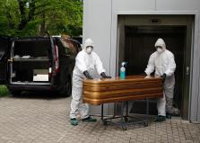 Trabajadores de un tanatorio sacan del hospital un ataúd para proceder a su desinfección antes de trasladarlo al cementerio