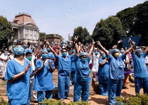 El personal del hospital de Victoria agradece que un helicóptero de la Fuerza Aérea de la India dispersa flores para rendir homenaje a los trabajadores de salud que hacen frente a la pandemia del coronavirus en Bangalore,