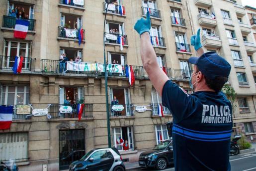 Un oficial de policía aplaude frente a un edificio decorado con banderas francesas y mensajes de apoyo para los empleados de salud mientras los vecinos aplauden desde sus ventanas para apoyar al personal médico francés.