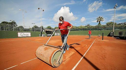Dos empleados trabajan en las pistas de tenis del Sporting Club Portals.