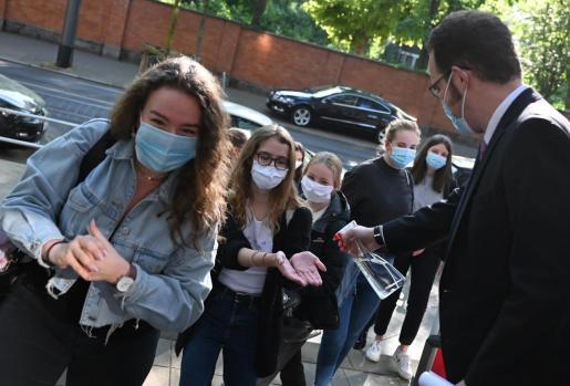 Un grupo de jóvenes se higieniza las manos antes de entrar a clase en Frankfurt.