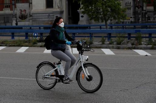 Una mujer se desplaza en bicicleta en España, en el inicio de la desescalada.