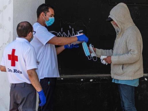 Voluntarios de Cruz Roja entegan guantes y mascarillas a un indigente en Llucmajor.