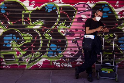 Un ciudadano consulta su teléfono móvil frente a un comercio cerrado en España.