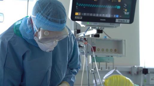 Un sanitario, atiende a un paciente con coronavirus, ingresado en un hospital.