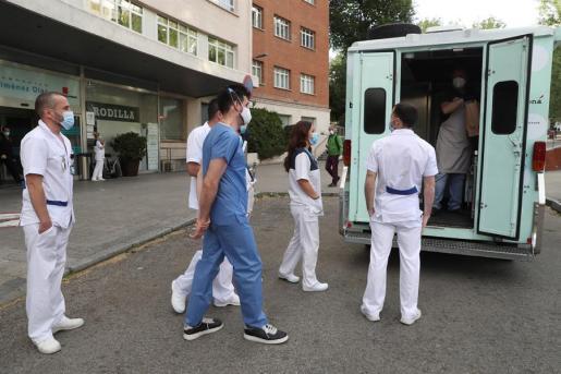 Varios profesionales sanitarios se acercan a una ambulancia.