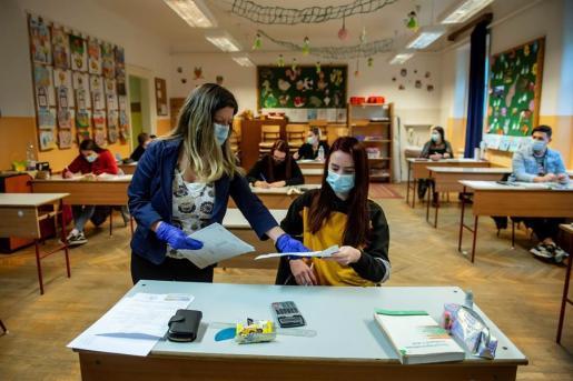 Una profesora y una alumna, protegidas, en la vuelta a las aulas en Hungría.