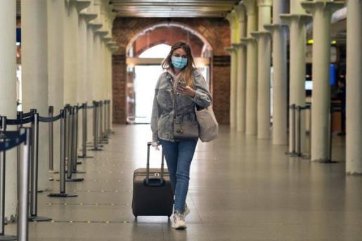 Una mujer utiliza mascarilla para protegerse del coronavirus.