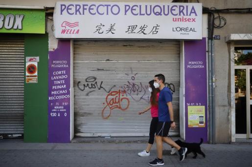 Dos jóvenes paseando por una calle de Palma.