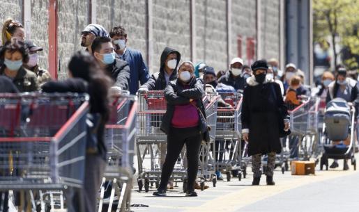 Gente haciendo cola con mascarillas en Nueva York.