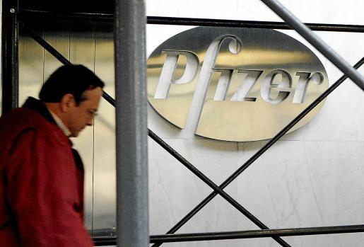 Imagen de archivo de un peatón que pasa junto al logo de la farmacéutica Pfizer Inc., en su sede de Nueva York.