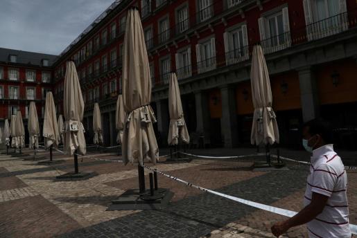 Un hombre paseando con mascarilla por la Plaza Mayor de Madrid.