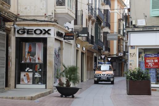 Imagen de un vehículo circulando por una calle comercial de Palma completamente vacía.